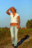 Blonde woman. Happy beautiful blonde woman on the country road with blue jeans and white shirt royalty free stock photography