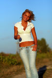 Blonde woman. Happy beautiful blonde woman with blue jeans and white shirt smiling royalty free stock photos