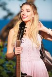 Blonde woman with acoustic guitar on seaside stock image