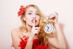 Blonde woman with alarm-clock. Portrait of beautiful blond lady holding alarm-clock in her left hand and showing silence sign. Calm lady in red dress looking at Stock Photo