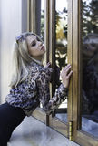 Blonde woman in animal print shirt leaning against store window Stock Photos