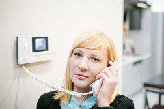 Blonde woman answers the intercom call Stock Photos