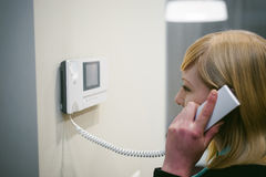 Blonde woman answers the intercom call Stock Photo