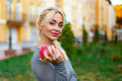 Blonde woman with apple Stock Photo