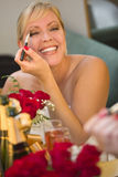 Blonde Woman Applies Makeup at Mirror Near Champagne and Roses Stock Images