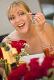 Blonde Woman Applies Makeup at Mirror Near Champagne and Roses Stock Image