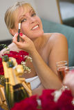 Blonde Woman Applies Makeup at Mirror Near Champagne and Roses Royalty Free Stock Images