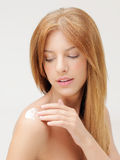 Blonde woman applying body lotion on shoulder Stock Photos