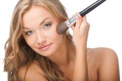 Blonde woman applying powder on face Stock Photos