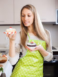 Blonde woman in apron with cakes Royalty Free Stock Photos
