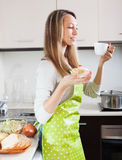 Blonde woman in apron drinking tea Stock Image