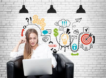 Blonde woman in armchair, business plan, brick Royalty Free Stock Image