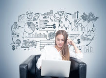 Blonde woman in armchair, business plan, gray Royalty Free Stock Photography