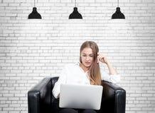 Blonde woman in armchair, laptop, brick Stock Photo