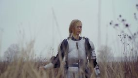 Pensive Jeanne d`Arc in medieval armor. A blonde woman in armor with a sword in her hand is standing in the field with a cloudy day stock video