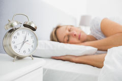Blonde woman asleep in bed while her alarm shows the early time Stock Photos