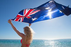 Blonde woman Australian flag at ocean royalty free stock images