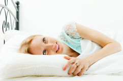 Blonde woman awaking in her bed at home Stock Image
