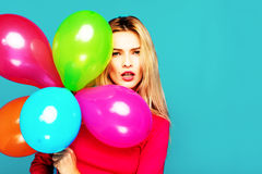 Blonde woman with balloons on blue. Beautiful blonde woman very energetic, smiling and holding some colored balloons on blue background Stock Images