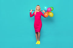 Blonde woman with balloons on blue. Beautiful blonde woman very energetic, smiling and holding some colored balloons on blue background Royalty Free Stock Photos