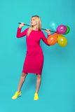 Blonde woman with balloons on blue. Beautiful blonde woman very energetic, smiling and holding some colored balloons on blue background Royalty Free Stock Images