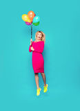 Blonde woman with balloons on blue. Beautiful blonde woman very energetic, smiling and jumping with some colored balloons on blue background Stock Photos