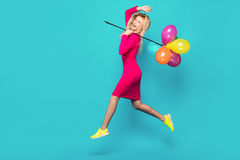 Blonde woman with balloons on blue. Beautiful blonde woman very energetic, smiling and jumping with some colored balloons on blue background Royalty Free Stock Image