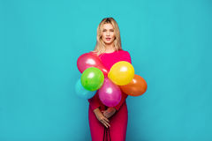 Blonde woman with balloons on blue. Beautifull blonde woman very energetic, smiling and holding some colored balloons on blue background Stock Images