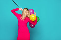 Blonde woman with balloons on blue. Beautifull blonde woman very energetic, smiling and holding some colored balloons on blue background Royalty Free Stock Photo