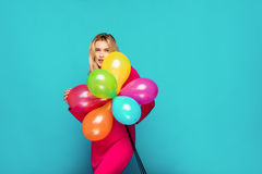 Blonde woman with balloons on blue. Beautifull blonde woman very energetic, smiling and holding some colored balloons on blue background Royalty Free Stock Images