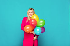 Blonde woman with balloons on blue. Beautifull blonde woman very energetic, smiling and holding some colored balloons on blue background Stock Photos