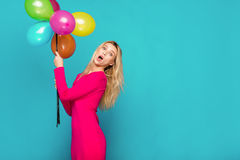 Blonde woman with balloons on blue. Beautifull blonde woman very energetic, smiling and holding some colored balloons on blue background Royalty Free Stock Photos