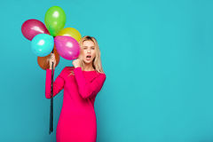 Blonde woman with balloons on blue. Beautifull blonde woman very energetic, smiling and holding some colored balloons on blue background Stock Photo