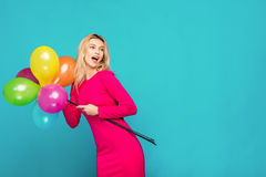 Blonde woman with balloons on blue. Beautifull blonde woman very energetic, smiling and holding some colored balloons on blue background Stock Image