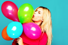 Blonde woman with balloons on blue. Beautifull blonde woman very energetic, smiling and holding some colored balloons on blue background Stock Photography