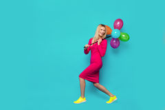 Blonde woman with balloons on blue. Beautifull blonde woman very energetic, smiling and holding some colored balloons on blue background Royalty Free Stock Photography
