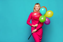 Blonde woman with balloons on blue Royalty Free Stock Images