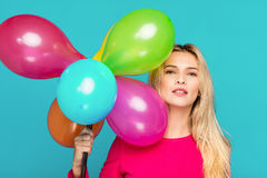 Blonde woman with balloons on blue. Beautifull blonde woman very energetic, smiling and holding some colored balloons on blue background Royalty Free Stock Image