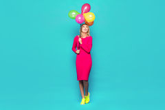 Blonde woman with balloons on blue. Beautifull blonde woman very energetic, smiling and jumping with some colored balloons on blue background Royalty Free Stock Photos