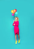 Blonde woman with balloons on blue. Beautifull blonde woman very energetic, smiling and jumping with some colored balloons on blue background Royalty Free Stock Photography