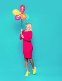 Blonde woman with balloons on blue. Beautifull blonde woman very energetic, smiling and jumping with some colored balloons on blue background Royalty Free Stock Image