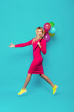 Blonde woman with balloons on blue. Beautifull blonde woman very energetic, smiling and jumping with some colored balloons on blue background Stock Photography