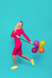Blonde woman with balloons on blue. Beautifull blonde woman very energetic, smiling and jumping with some colored balloons on blue background Royalty Free Stock Photo