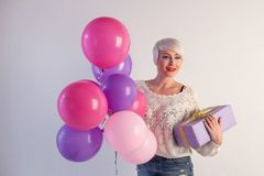 Blonde woman with balloons and gifts for holiday stock images