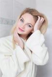 Blonde woman in bathrobe at bathroom. Freshness at morning Stock Image