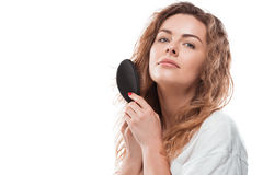 Blonde woman in bathrobe combing hair and looking at camera Stock Image