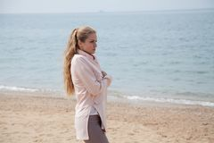 Beautiful blonde woman on the beach is cool stock photography
