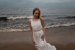 Walking Beautiful young blonde woman beach nymph in white dress near sea with waves during a dull gloomy weather with royalty free stock image