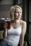 Blonde Woman with Beautiful Blue Eyes Drinking Glass of Pale Ale royalty free stock photo