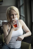 Blonde Woman with Beautiful Blue Eyes Drinking Glass of Pale Ale Royalty Free Stock Image
